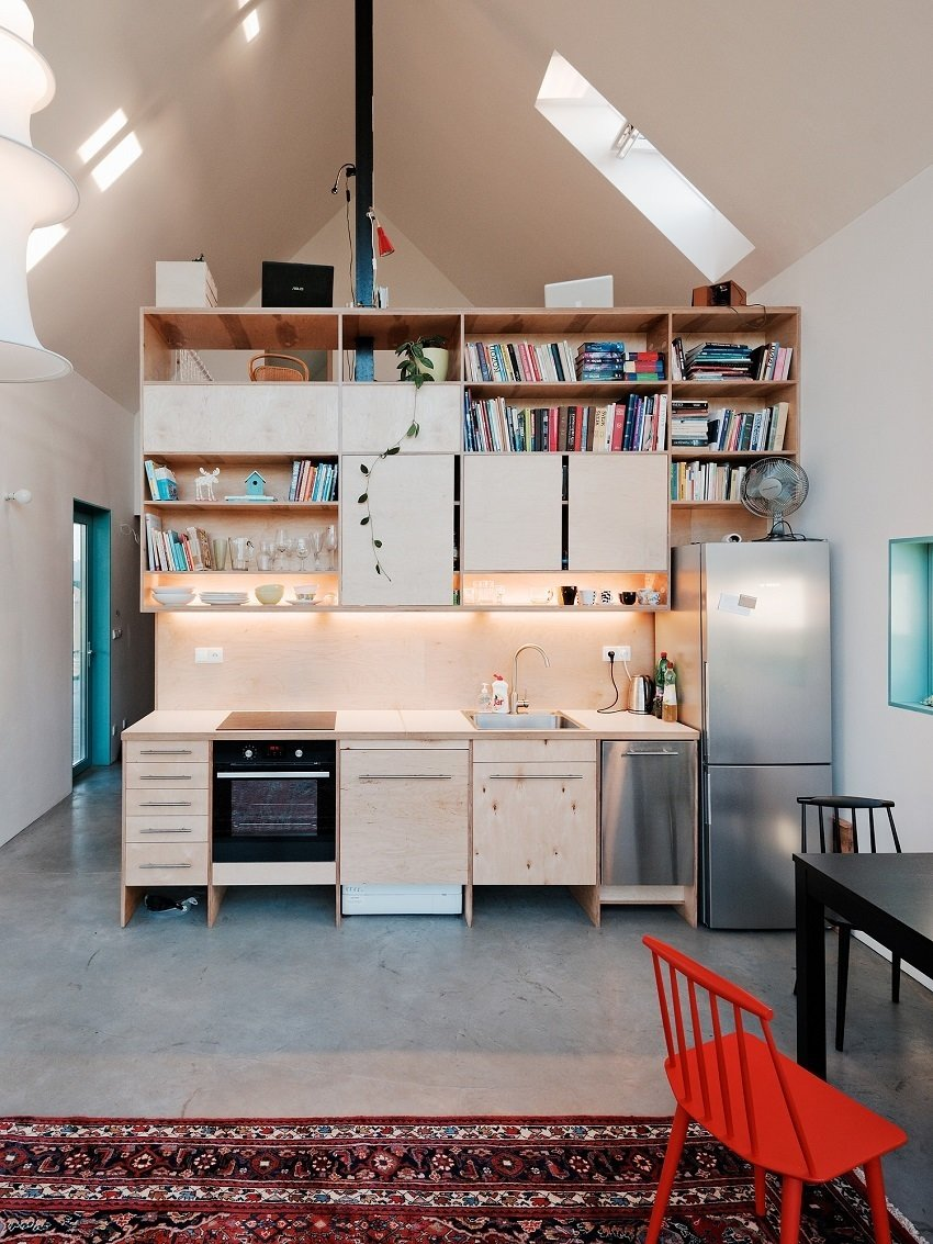 """Kitchen, Rug Floor, Concrete Floor, Pendant Lighting, Wood Cabinet, Cooktops, Wood Counter, Dishwasher, Drop In Sink, Open Cabinet, Wood Backsplashe, Accent Lighting, Wall Oven, and Refrigerator Inside, the custom-built casework and splashes of blue and red stand out. Jurkovič designed a central """"service box"""" on the ground floor, so open space wraps around the plywood-encased core which contains the kitchen, bathroom, toilet, stairs, and storage.  Photo 4 of 8 in Small Country Home with Dramatic See-Through Wall"""