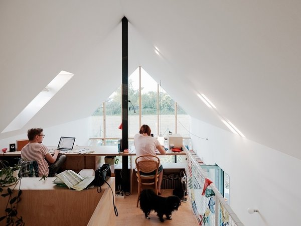 Office, Chair, Medium Hardwood Floor, and Desk Balanced above the central core, the office offers an ideal perch for work with a west-facing skylight that provides natural illumination for the shared desk space.  Photo 7 of 8 in Small Country Home with Dramatic See-Through Wall