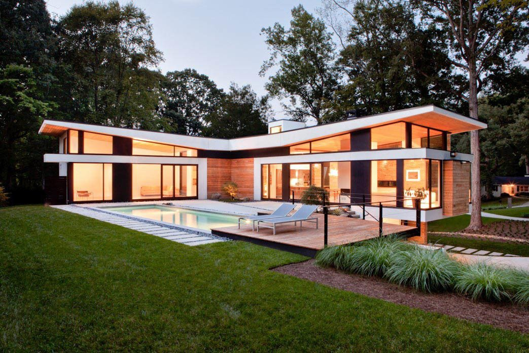 "The home's T-shaped layout forms a courtyard accessible by its two ""social wings,"" fitted with massive Kawneer sliding doors made for auto showrooms.  Photo 3 of 7 in A Wing-Roofed Home in Georgia Perches Among the Trees"