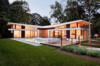 """The home's T-shaped layout forms a courtyard accessible by its two """"social wings,"""" fitted with massive Kawneer sliding doors made for auto showrooms."""
