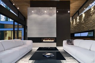 The clients asked for interior products in thirteen shades of white, including the twin Malibu sofas by American Leather. Interior designer Burns Century added deeply hued textures such as the charcoal suede on the fireplace column to keep the room feeling natural, not icy. The black Pool coffee tables are from Design Within Reach.