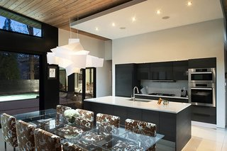 Candy Sarvis loves feeling connected with dinner guests while she cooks. The African teak kitchen cabinetry is by Pedini, with Miele appliances. A Big Bang pendant by Foscarini illuminates the Montecarlo table by Cattelan Italia.