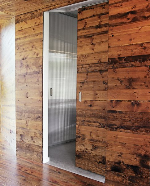 Doors, Interior, and Sliding Door Type The wooden doors in the living room practically vanish when closed. Sliding them open reveals modern bedroom suites in a lighter, brighter palette.  Photo 3 of 10 in 10 Modern Barn Door Ideas You Wouldn't Expect