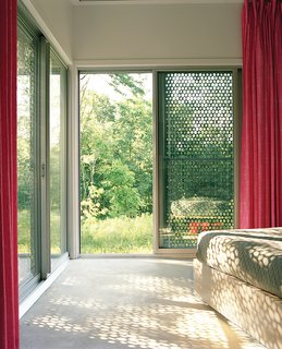 Perforated metal on the exterior of this home filters light coming in, providing shade and a desired aesthetic effect on the interior and exterior.