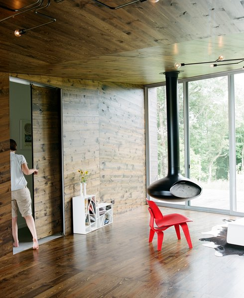 Though minimal, the furnishings in the living room each make a statement. The red molded plywood Eames chair for Herman Miller sits within warming distance of the suspended fire orb.