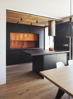 Joaquin Altamirano and Silvia Martín worked with Daniel Bergman Vázquez of Estudio Untercio to create an open-plan oasis in an apartment building in central Madrid. Estudio Untercio designed the medium-density fiberboard cupboards, which are coated with lacquer paint matching the ceramic-porcelain countertops. The tubular hood above the island is by Teka.