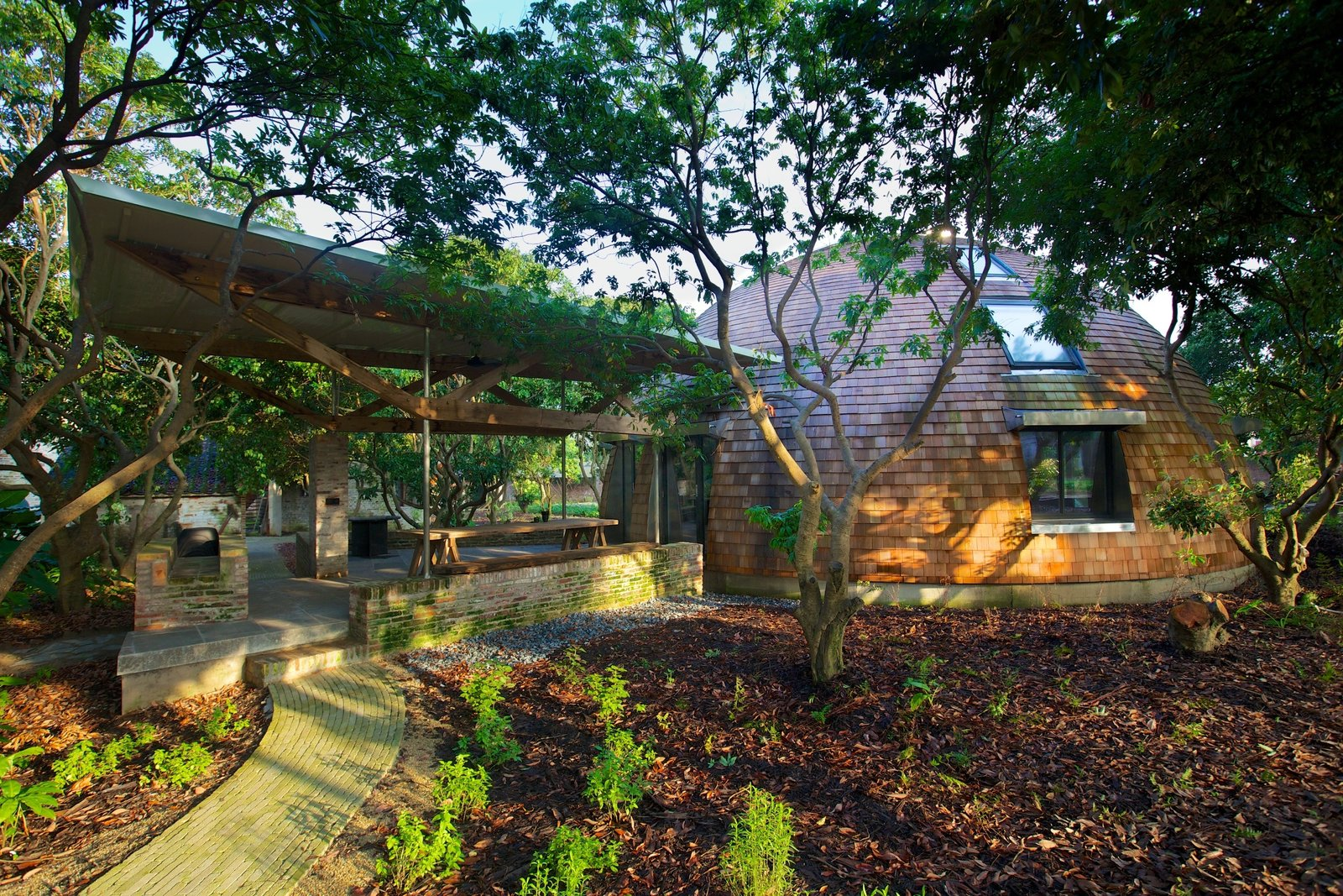 Clad in red shingles, the house's titular dome is located in the midst of a lychee garden. All of its parts have been neatly fitted together, allowing the home to meet German Passive House standards and keeping energy consumption to a minimum. The benches, walls, and frame for the outdoor seating area were built from reclaimed wood and brick.  Photo 1 of 8 in A British Furniture Brand Built This Round Village in China