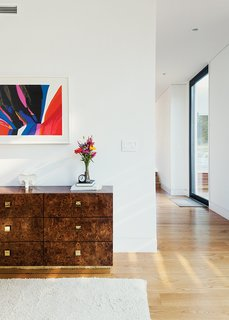 Cute Couple Alert: Modern Prefab Poolhouse Addition to a 1920s Sears Kit House - Photo 2 of 11 - The 1970s burlwood dresser is originally from a Palm Beach estate. Modernist sculptures throughout the house are by artist Costantino Nivola; abstract artwork is by Charles Schorre.