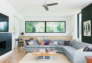 Cute Couple Alert: Modern Prefab Poolhouse Addition to a 1920s Sears Kit House - Photo 3 of 11 - The great room has a collection of vintage furniture finds, including a 1980s burled-elmwood-and-chrome coffee table found on Ebay. The sofa was another secondhand score, believed to be a 1950s Edward Wormley piece for Dunbar. Newer additions are a jute rug from overstock.com and a side table from Target.