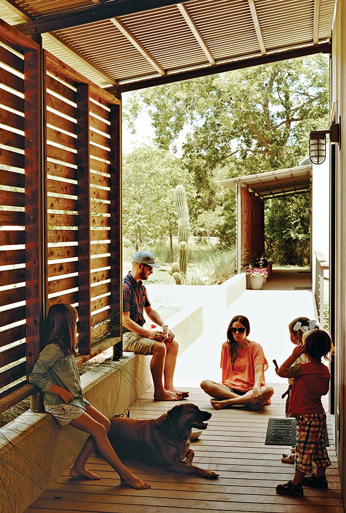 Outdoor and Wood Patio, Porch, Deck Red-cedar screens shade the modules' western walls, and part of the walkway that connects them, from the Texas sun.  Photo 9 of 11 in Modular Compound is the Ultimate Retreat for Three Generations