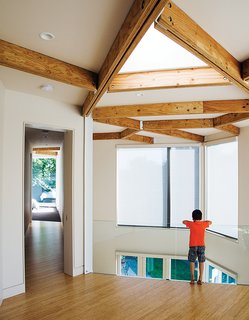The couple's son, Rio, pauses on the mezzanine, which leads to the bedrooms.