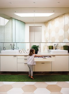 Hexagonal tiles made by the Portland Cement Company continue the pattern in the bathroom, where the architect designed low drawers and cabinets that are easy for Luna to reach.