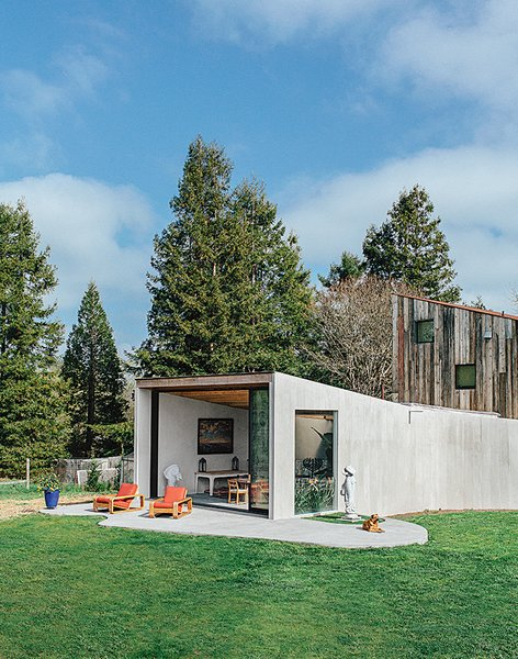 An unusually shaped structure in Sonoma, California features a teeming interior courtesy of generously sized skylights and a floor-to-ceiling wall of windows.
