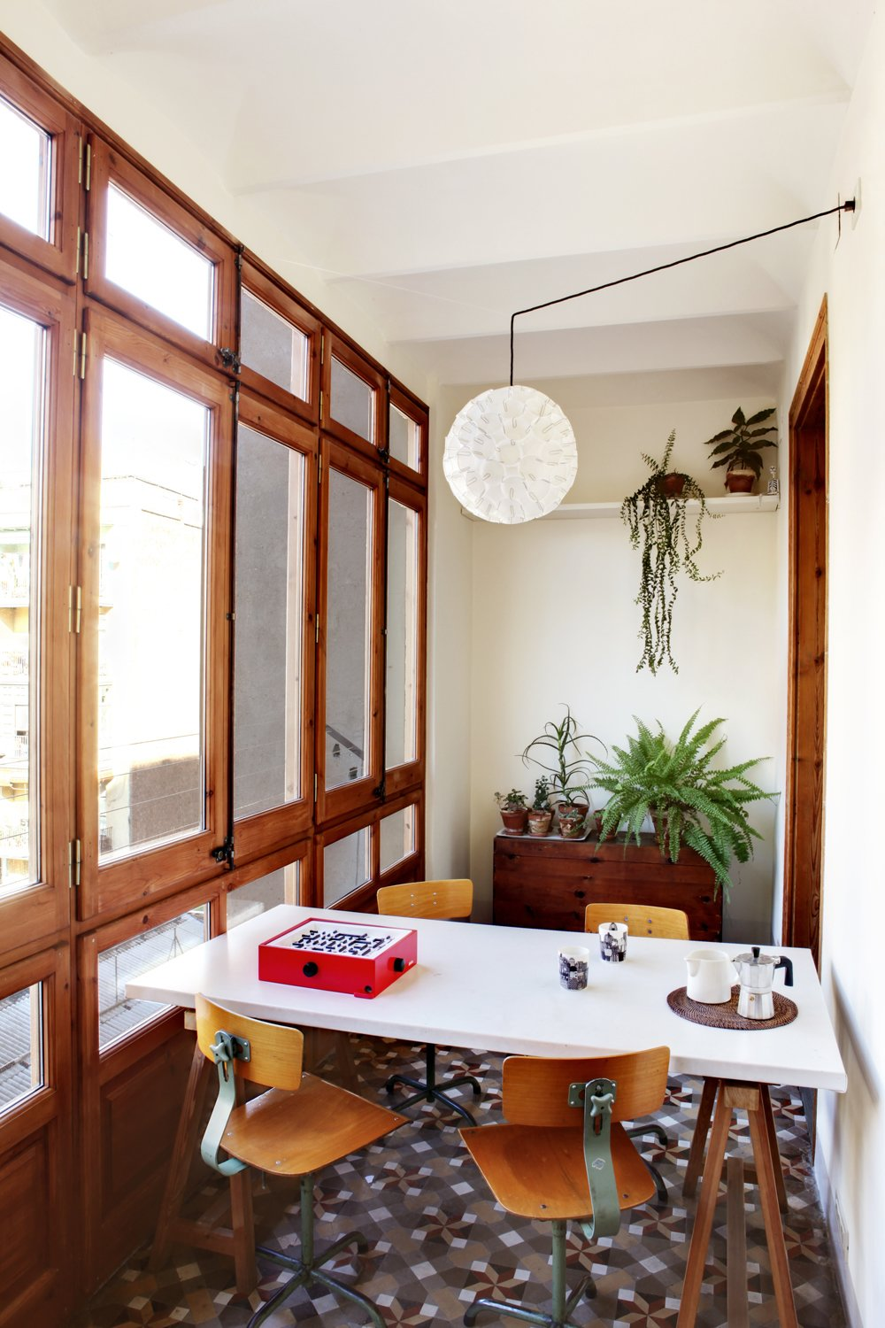 A glazed veranda on the flat's west side offers a cozy spot to enjoy an espresso. The utilitarian table and chairs were purchased second-hand, while the lamp was custom designed.  Photo 5 of 8 in Historic Details and Playful Modernism Meet in this Stunning Barcelona Flat