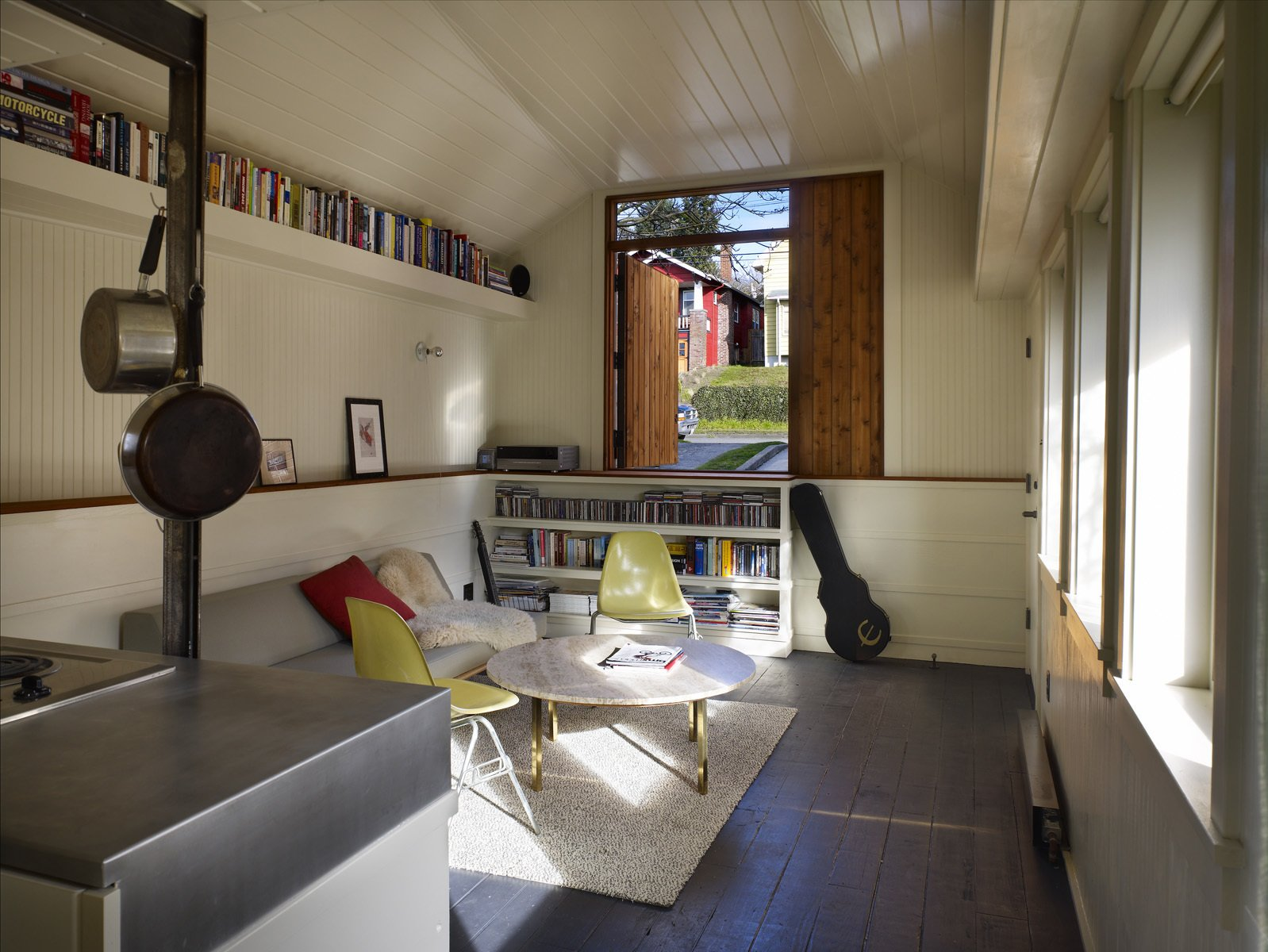 """Shed & Studio and Storage Space Room Type The compact rental features plenty of wooden ledges, nooks, and shelves for keeping belongings organized. In the living room, a low white wall is capped with fir wood salvaged from the garage's former posts. On the east wall, a half-door made of reclaimed cedar looks out on a garden.  """"It looks and lives a lot bigger than it is,"""" Schaer says.  Photo 5 of 8 in Tiny 1920s Garage Transformed Into a Charming Studio"""