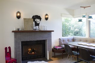 A husband-and-wife design team revived a 1940s home in East Los Angeles's Mt. Washington area for a single man. Bearing few tell-tale signs of bachelorhood, aside from a photography and music studio in the garage, the renovation retained the home's dual fireplaces and added an array of modern tiles. A transformed modern fireplace surrounded by Japanese tile flanks a custom banquette table in the dining/kitchen area.