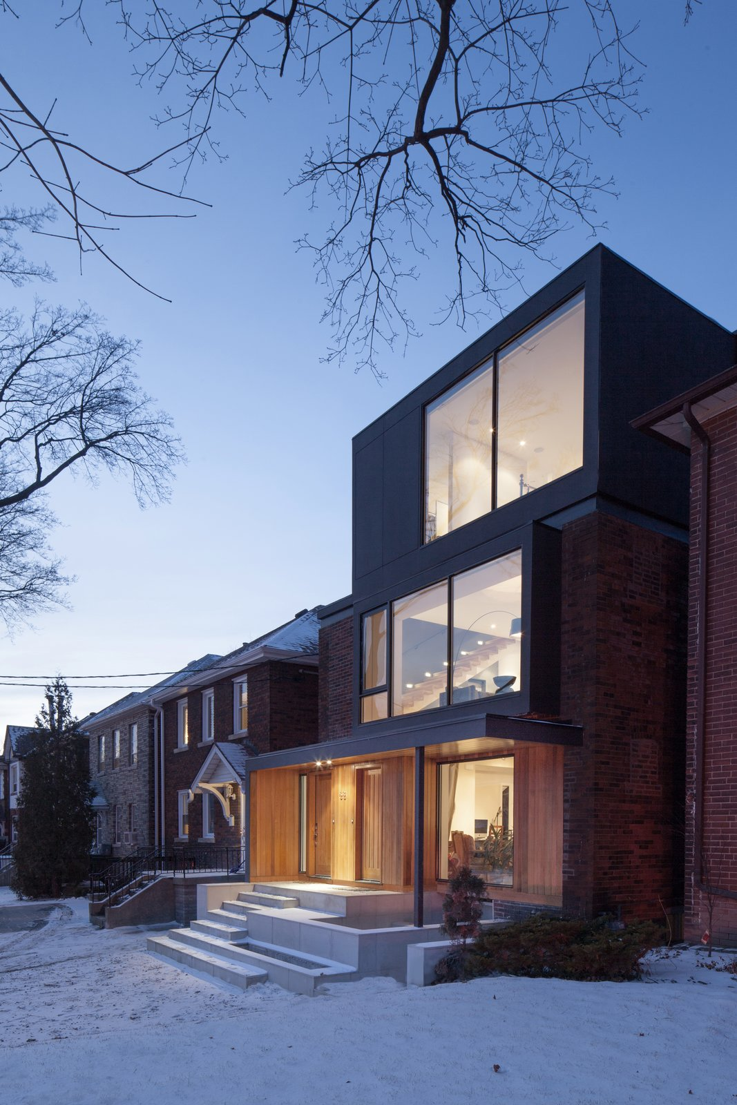 Viewed from the street, the triplex's brick wall and raised porch echo its neighbors' visual cues. Its dark grey, Extira-clad upper level and bay window, however, hint at the expansive spaces that lie within. Full-height windows allow light to stream in on all three levels.  Photo 1 of 9 in A Spacious Toronto Triplex Responds to Rising Urban Density