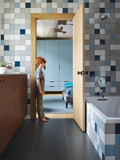 """Rock stands in the doorway to the boys' bathroom, which is lined with semi-gloss Modern Dimensions tiles from Daltile. """"We wanted it to be playful,"""" Hufft says, """"so we chose each color and laid out the tile distribution in Photoshop."""""""