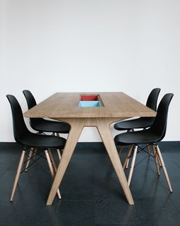 "Paired with Eames side chairs, her dining table includes two cases ""to either hide or show things,"" she says."