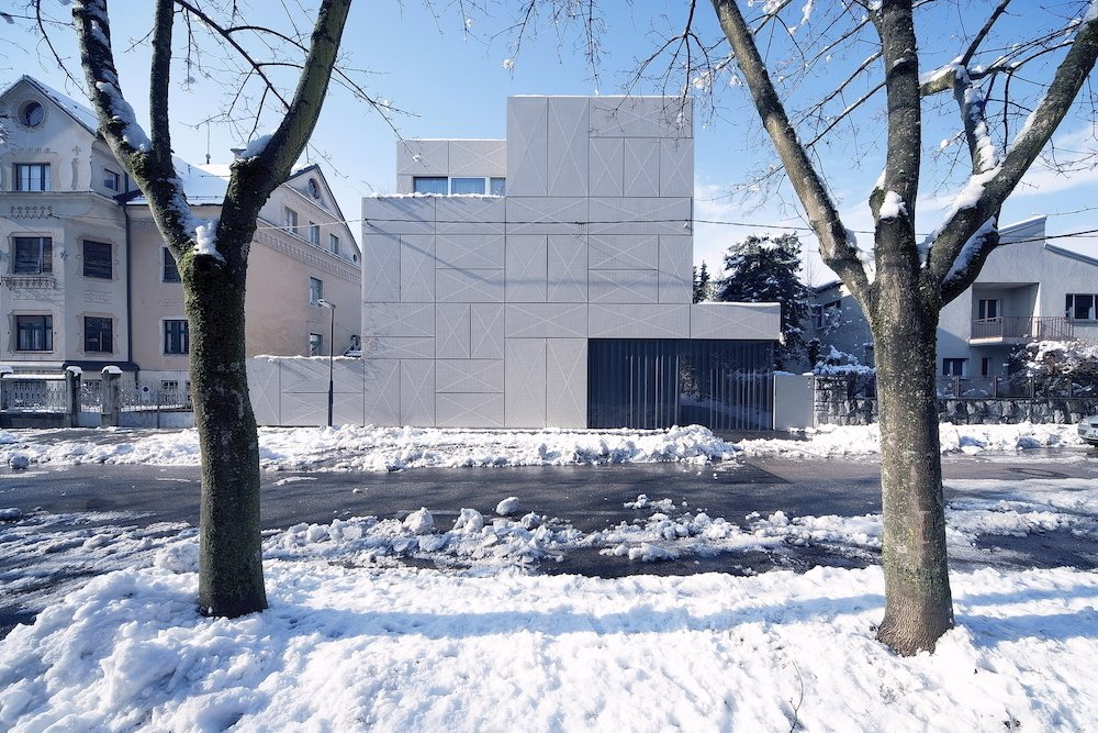 Exterior and House Building Type Rok Oman of OFIS Architects started the renovation of what would become Villa Criss-Cross by tackling a thorny site issue. Since it is located close to the street and perpendicular to the old Roman wall near Ljubljana's ancient fortress, zoning laws require buildings to be set four meters back from the street. By maintaining the original wall and adding steel panels, Oman grandfathered in the new structure and maintained the original orientation.  Photo 1 of 10 in Super Minimal Steel and Concrete Villa with an Unusual Facade