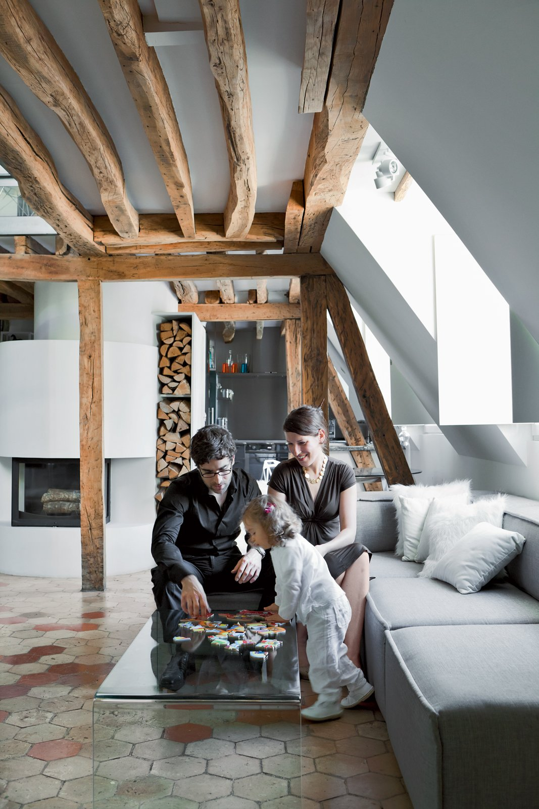 Living Room, Ceramic Tile Floor, Wood Burning Fireplace, and Sofa Herrman, his wife, Cécile, and their young daughter, Rose, play on the Pont table by Ligne Roset . The Carmo sofa is by Anders Nørgaard for BoConcept.  Photo 5 of 10 in 10 Modern Renovations to Unique Homes in France from A Corbusier-Inspired Parisian Home