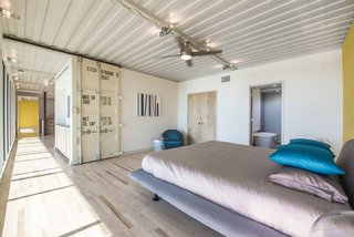 "The container doors are used as barn-style sliding doors that open up to the bedrooms. The house has a ""see-through nature,"" according to Gooden. It features a 66-foot unobstructed view along the window wall from one end to the other."