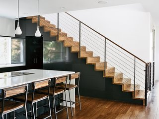 The Dora pendant lights in the kitchen are from Rejuvenation; quartz countertops are by Cambria and the custom bar stools are by Rocky Mountain Table Company. In Situ Studio designed the solid walnut steps with custom steel rails, a walnut hand rail, and a removable baby gate.