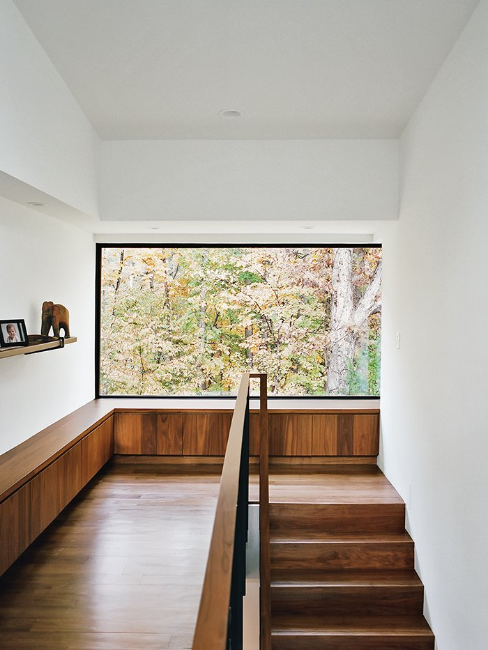 Staircase, Wood Railing, and Wood Tread Amy requested a quiet, sunny reading nook with a view; In Situ obliged with a built-in bench housing her collection of books.  Photo 8 of 13 in Minimal North Carolina Home Built for a Tech-Forward West Coast Couple
