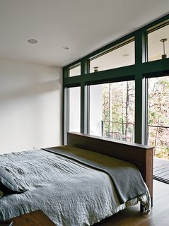 The master bedroom, which overlooks a lake across the street, is furnished with a Copenhagen bed by Wood Products for Room & Board.