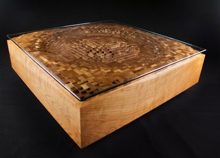 EndGrain's Ripple Coffee Table, shown here in cherry hardwood and glass, is a graphic representation of a the surface movement created by a ripple of water. Made up of cut squares of wood individually assembled back together, it is a good representation of the tension between natural and structure that often exists in Rupich's work.
