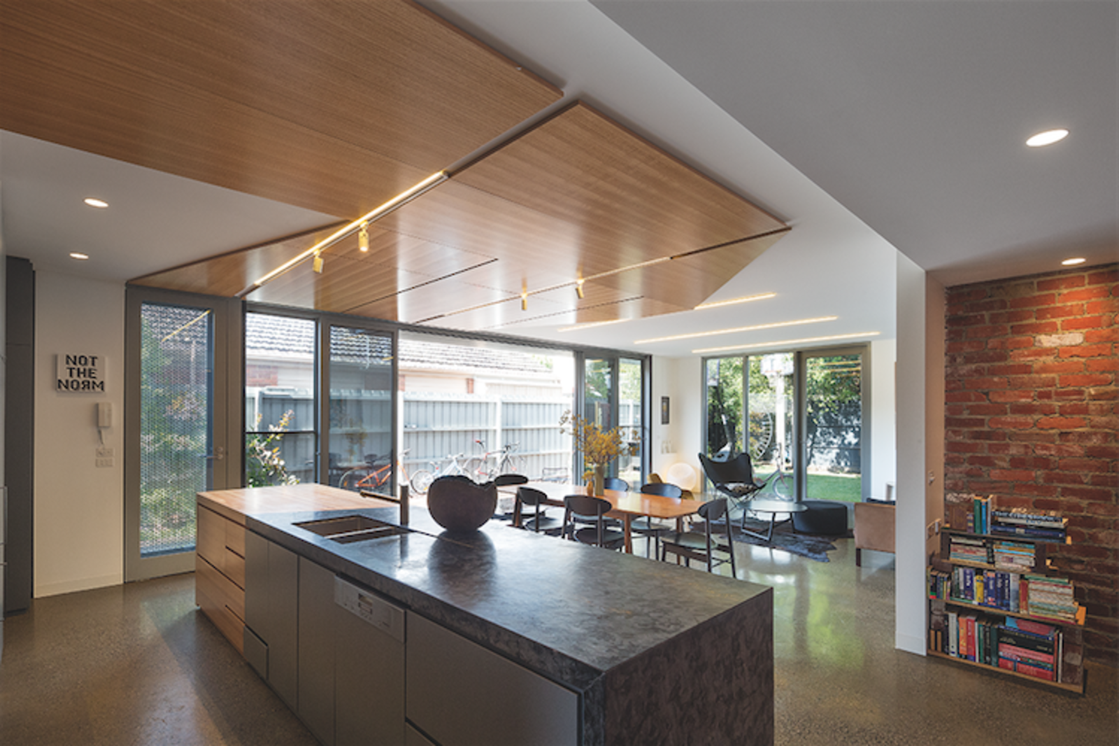 Windows and sliding glass doors extend the dining room space into the enclosed garden and maximize natural light inside.  Photo 3 of 7 in Angular Australian House Fits a Family's Active Lifestyle