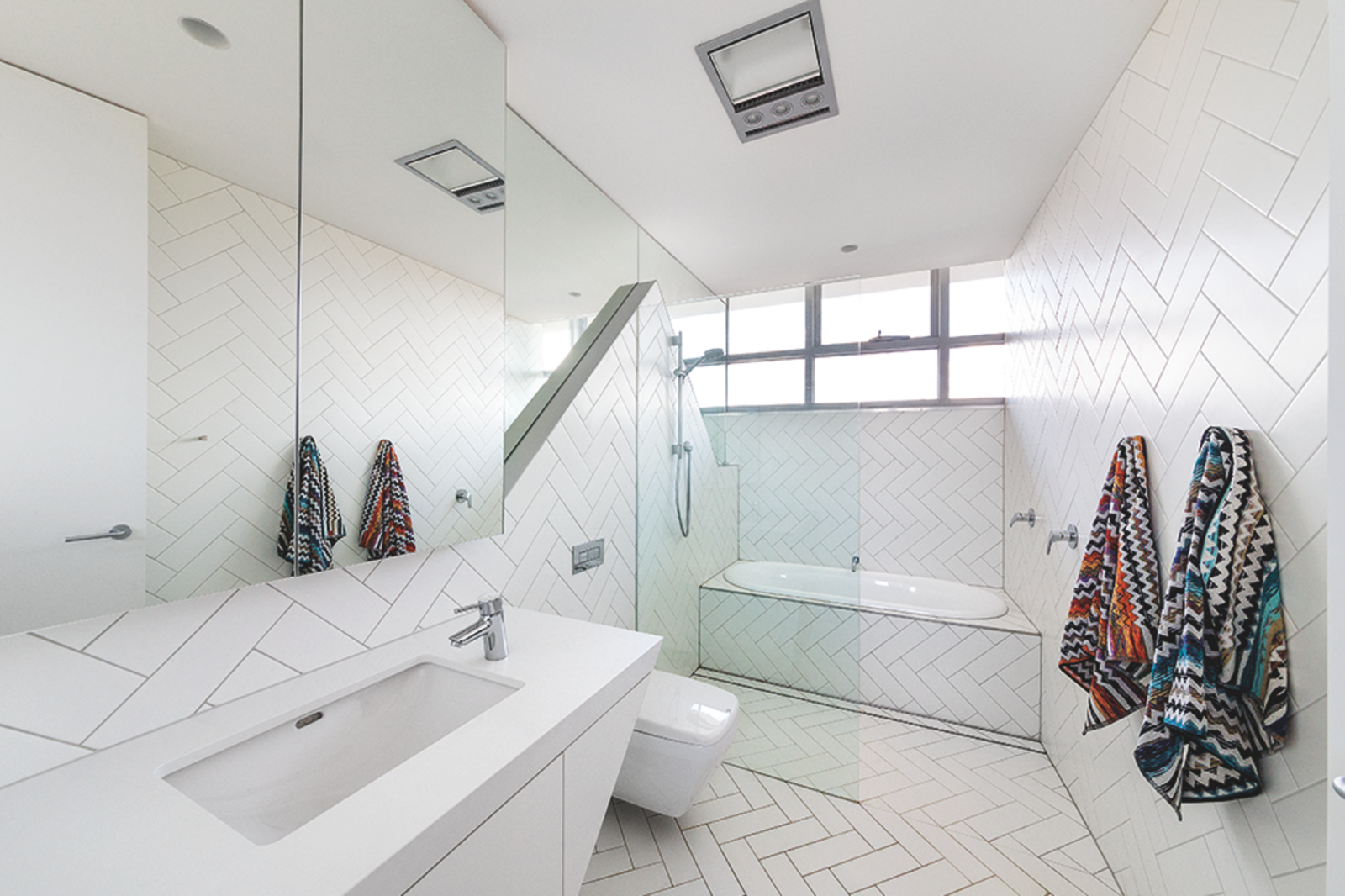 """The kids' bathroom is lined in clean white tile, which is arranged in a way that """"responds to the twisting and folding externally,"""" Dunn says.  Photo 5 of 7 in Angular Australian House Fits a Family's Active Lifestyle"""