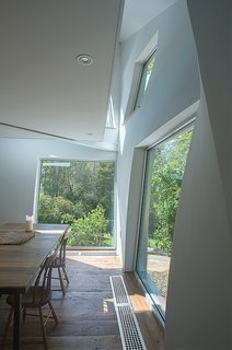 A suspended balcony on the second floor lets light pass easily through the house.