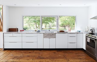The new custom kitchen is situated in the original structure. The window is a new commercial unit with an operable frameless center pane and was set so that the countertop could tuck right underneath it to create a 1/4-inch shadow line.