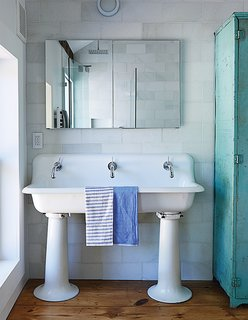 The bathroom features a salvaged 1920s schoolhouse sink from Olde Good Things. The faucet mixers are by Jado; the original single tap openings were enlarged to fit them, and the entire sink was re-glazed.