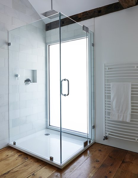 A glass-lined shower with a Hudson Reed shower head adds a modern touch to the second-floor bathroom in this farmhouse renovation. A pane of privacy glass lets natural light enter the room, illuminating the shower stall.