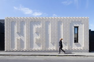 """This Victorian-era home in Melbourne, renovated by OOF! Architecture, maintains privacy from the street, but does so in an unusually """"friendly"""" manner—with a giant brick wall that spells out """"Hello,"""" a collaboration with local artist Rose Nolan. The residents wanted their house to appeal to passersby, since it sits on a well-trafficked block near a café."""