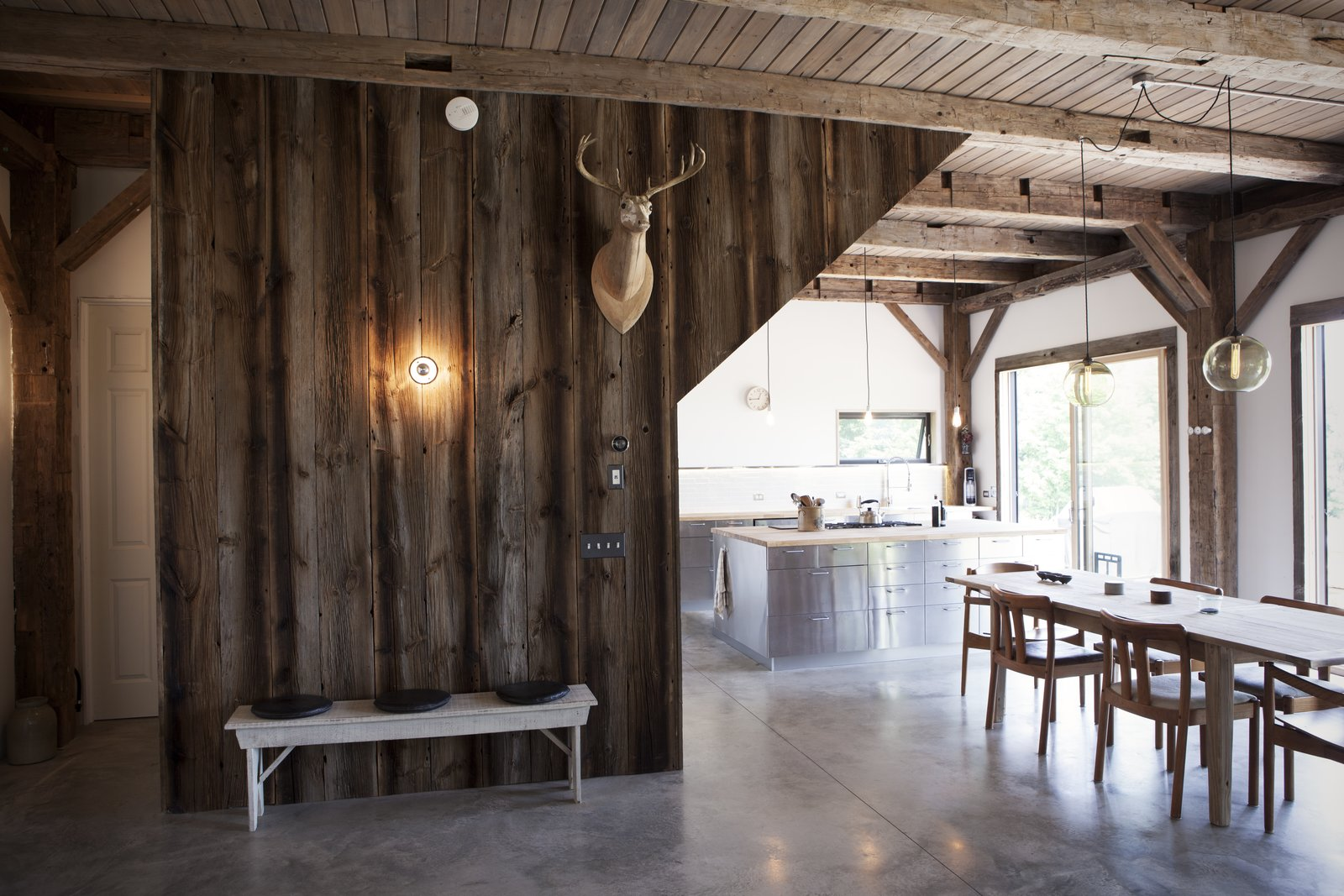 """Kitchen, Metal Cabinet, Concrete Floor, Pendant Lighting, and Wall Lighting The cabin's basic structure was reclaimed from a barn built in 1840 and purchased from Heritage Barns out of Waco, Texas. The same company supplied the recycled wood that clads the walls, though the ceiling boards are new. """"We stained them with a gray wash to match the tones of the post and beam, but with a more clean look,"""" Bronee explains. The concrete floors were polished and waxed for a sleek finish.  Photo 7 of 8 in 8 Beautiful Home Projects Using Reclaimed Wood from A Slice of Scandinavian Design in the Catskills"""