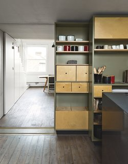 A sliding storage wall can be tucked aside to allow a seamless connection to the living and dining area.