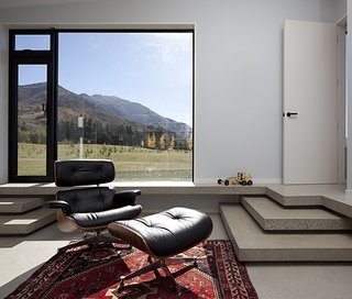 The clients intend to retire to the house. They asked that rooms be constructed flexibly on a non-domestic scale. This one, with an Eames lounge and floor-to-ceiling glass windows, frames a serene mountain vista like a painting.