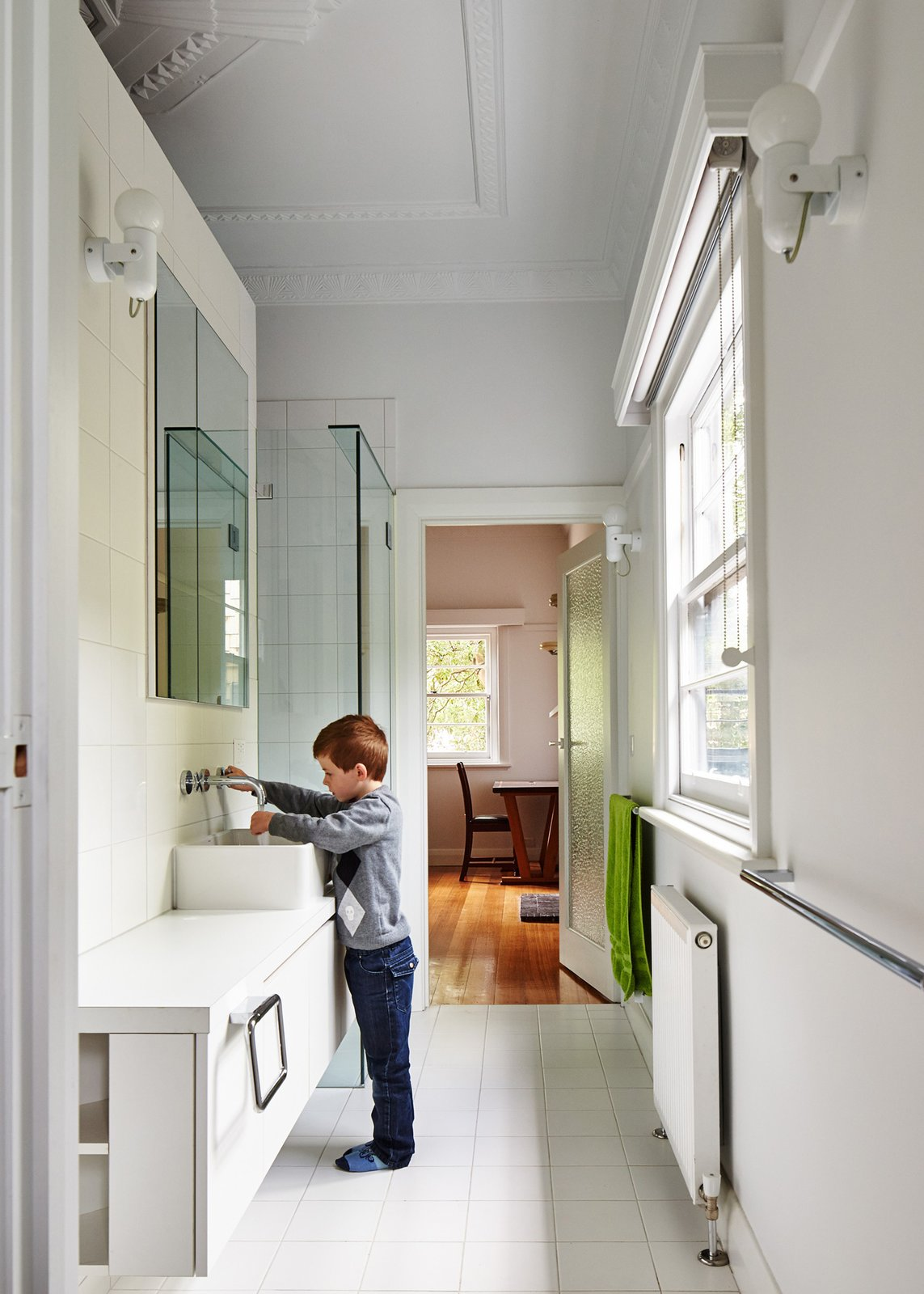 Bath Room, Vessel Sink, and Ceramic Tile Wall In the main bathroom, Art Deco crown molding reminds residents of the house's past. New fixtures include white laminate cabinets and sinks and faucets by Roger Seller.  Photo 5 of 12 in This Transformed Melbourne House Resembles a Quirky Village