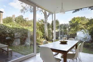 The dining area looks out directly at the garden with only a solitary hanging light interrupting sightlines. Eames fiberglass chairs surround the dining table. Pale finishes, including the wood flooring by Reclaimed Flooring Company, further augment the sense of airiness.
