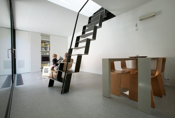 A welded-iron staircase with irregular treads sits at the center of this house in Ljubljana, Slovenia, by Dekleva Gregoric Architects. The iron treads are cut so that each step has an alternating angle, suggesting a climb that starts with the left foot, then the right. From a distance, the stair seems to form a black, angular, almost skeletal sculpture.