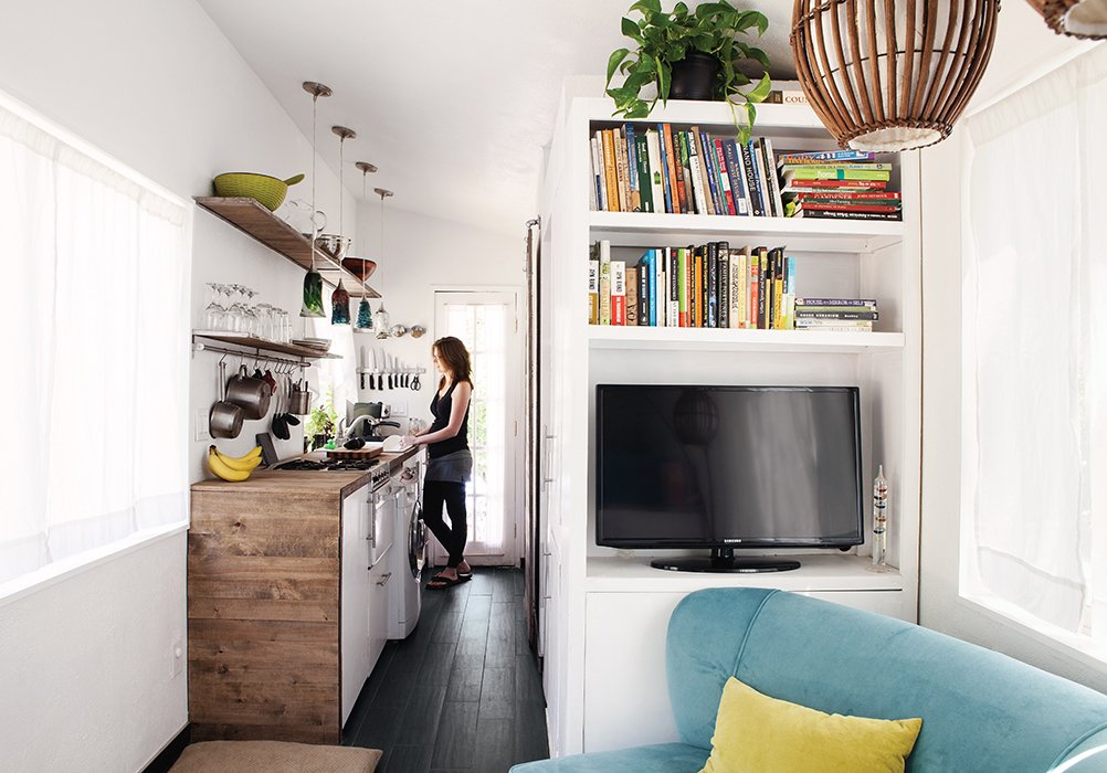 Living Room, Chair, Shelves, Dark Hardwood Floor, and Pendant Lighting An enthusiastic cook, Miller says she can easily work in the galley-style kitchen. The reclaimed-wood surround echoes the exterior cladding.  Photo 2 of 4 in Tiny House Fits a Family in 196 Square Feet