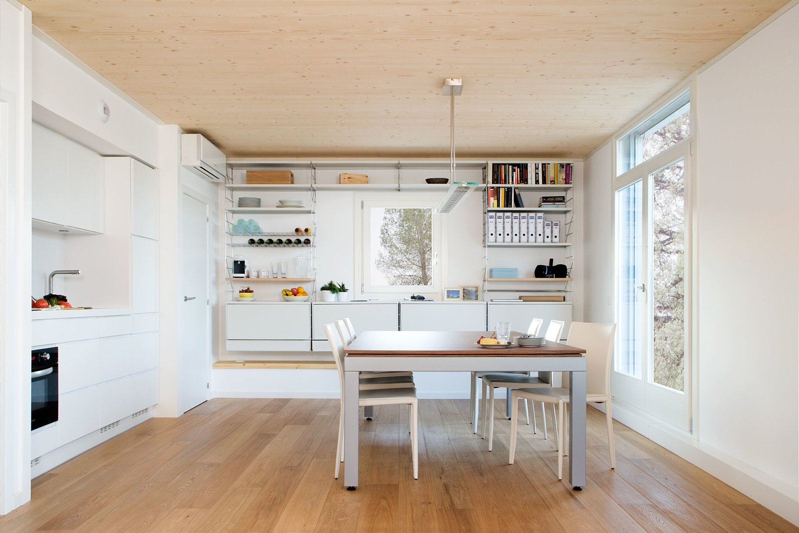 """Inside the home, soft oak flooring and the immaculate white walls and furniture """"maximize the sensation of light,"""" Martín says.  Photo 3 of 7 in Plugged-In Prefab Collects Weather Data to Conserve Energy"""