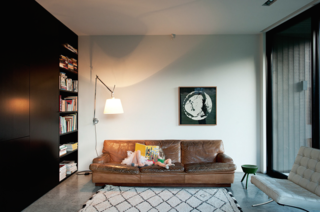 "The architect specifically chose a palette of natural finishes, including the polished concrete floor that flows the length and breadth of the ground level.<br><br>By way of contrast, the couple's eclectic collection of much-loved vintage furniture, including Mies van der Rohe Barcelona chairs, an Artemide lamp, and this 50-year-old sofa by mid-century Swedish designer Arne Norell, provide color and warmth. ""The bookcase also makes use of space to add layers of texture. Books are always a great addition to any interior,"" says Cooke.<br><br>The Beni Ouarain rug was purchased on a trip to Morocco."