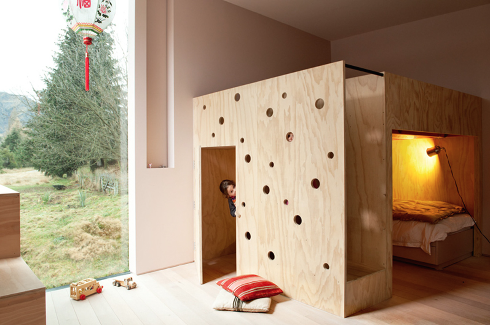 Kids Room, Bedroom Room Type, Bed, Light Hardwood Floor, Pre-Teen Age, and Toddler Age The combination bunk bed and playhouse is another whimsical gesture the architect designed specifically for her two daughters. The spaces are organized in such a way that they can play independently or together.  Photo 11 of 16 in 15 Modern and Creative Spaces For Kids from This Kid-Friendly Home is Full of Surprises