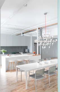 In a 1920s building on St-Dominique Street in Montreal, formerly a factory for canned soup, a sleek apartment for a family now stands. In the open-plan dining area, a Major Crown chandelier by Nemo hangs above a Zeus-Noto table and Kartell chairs.
