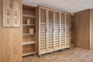 A Modular Meeting Room Features a Table with 6 Possible Layouts - Photo 5 of 6 - A wooden wardrobe provides storage, while a carved and burnt-wood board provides visual instructions explaining the room's possible configurations