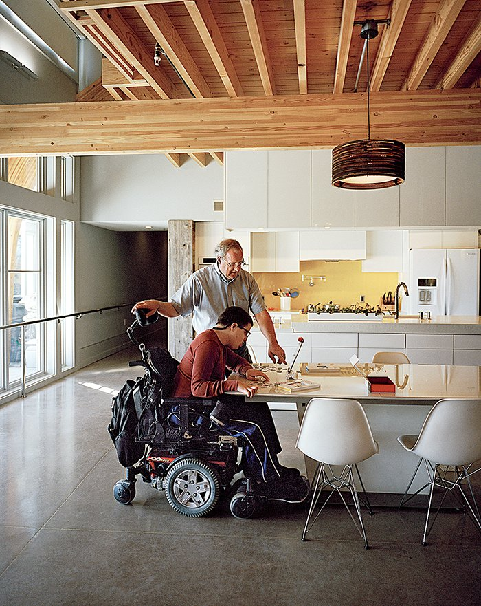 Dining Room, Table, and Chair Ed Slattery, seen here with his son Matthew, wanted to create a sustainable home that is accessible without feeling like a hospital.  Photo 3 of 8 in This Impressively Accessible Home Has a Tower That Can Be Reached by Wheelchair